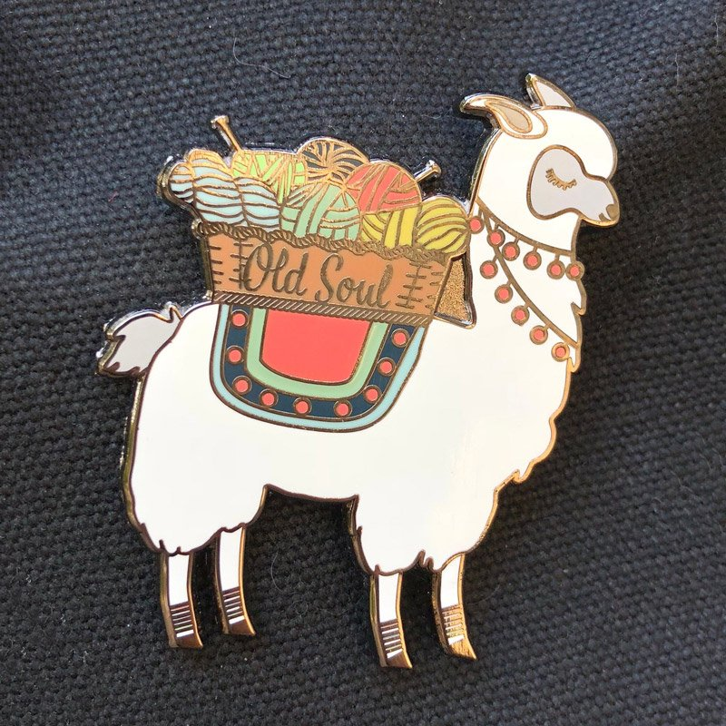alpaca with a basket of yarn on its back enamel pin