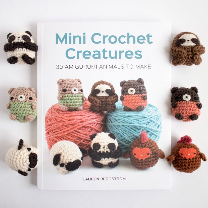 mini crochet creatures book with several amigurumi animals around it