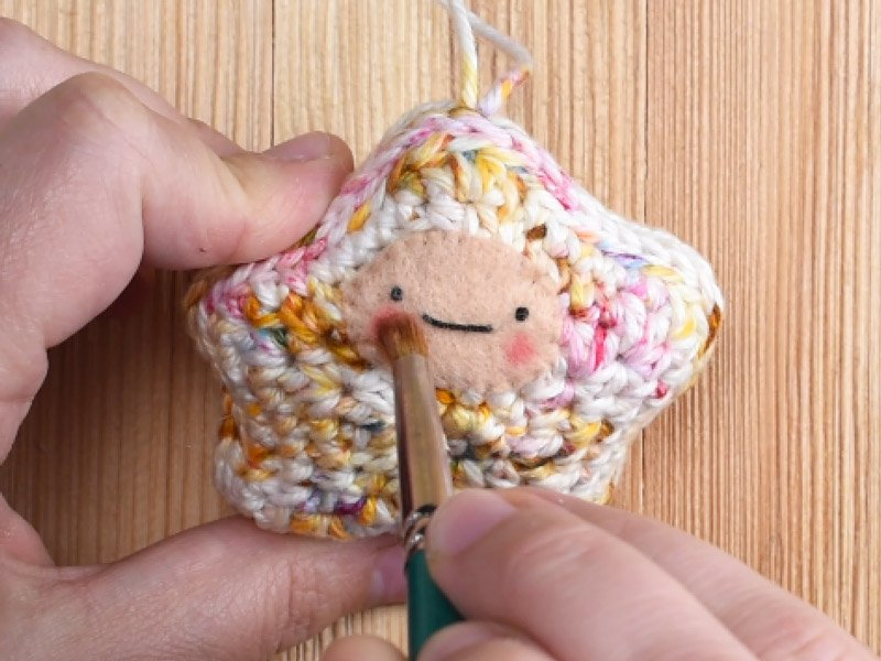 Applying blush to crochet star