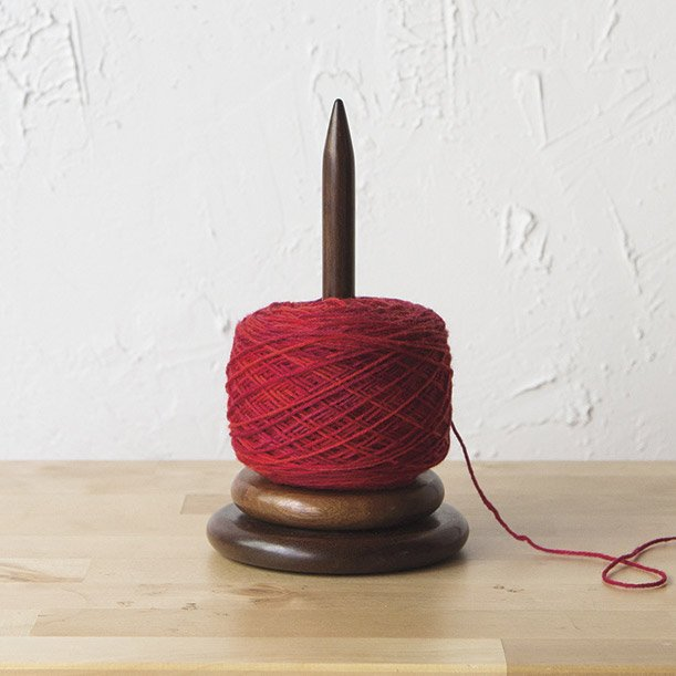 Wood yarn spindle with red yarn on it