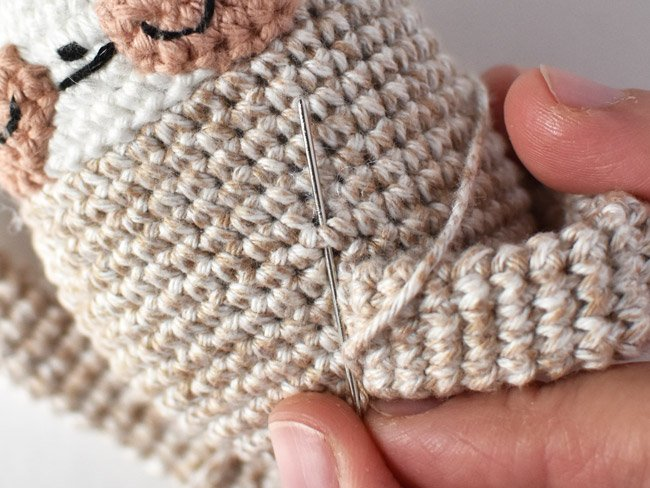 attaching the arm loop to the amigurumi sloth