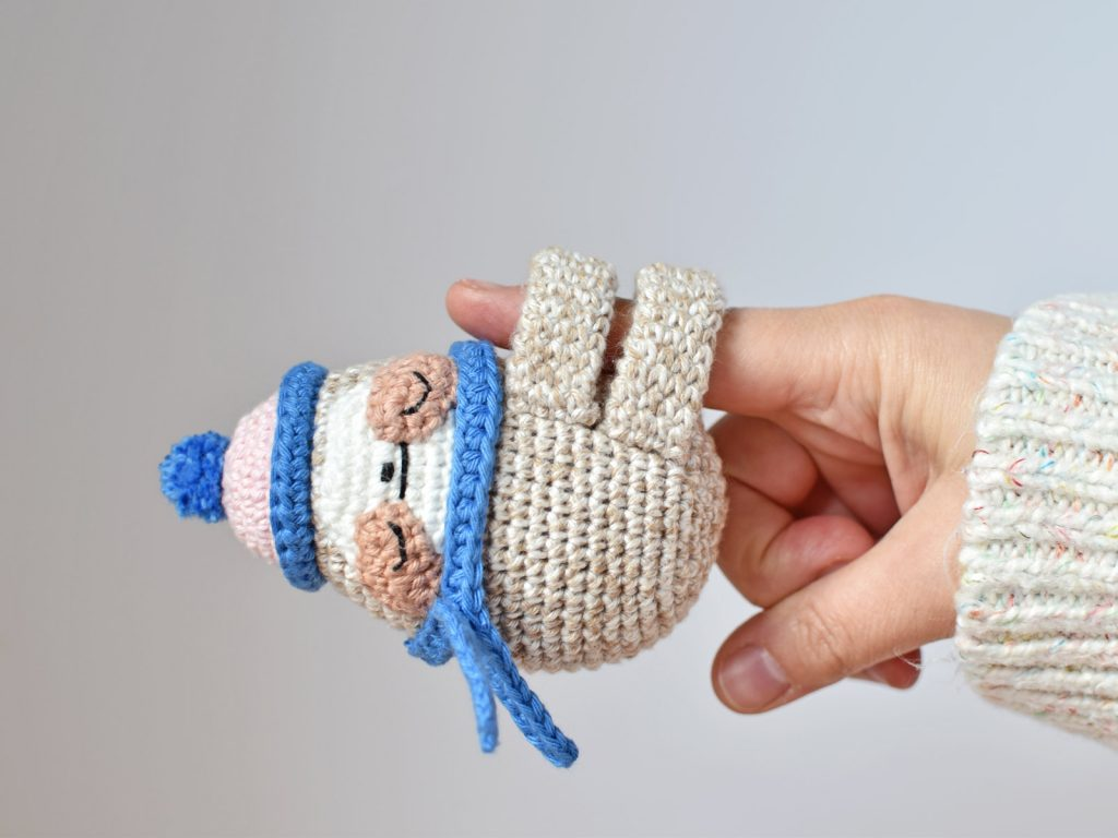 crochet sloth doll hanging from a finger