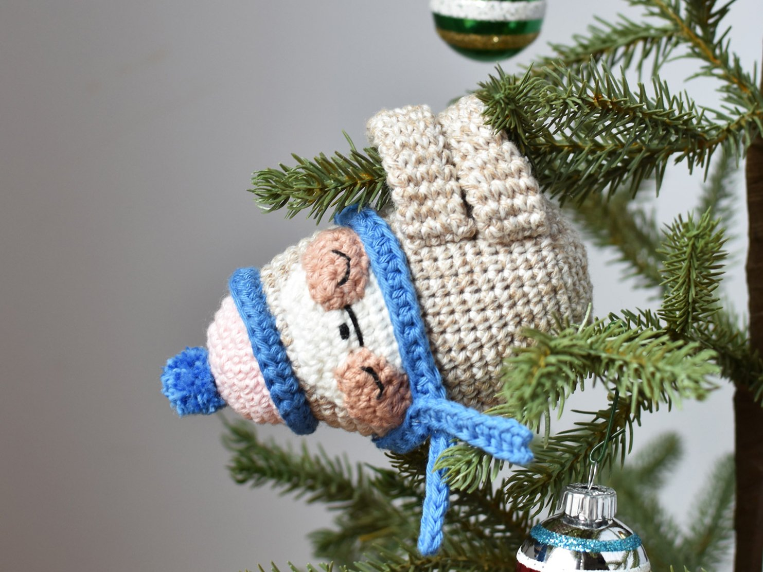 Sloth crochet Christmas ornament hanging from limb