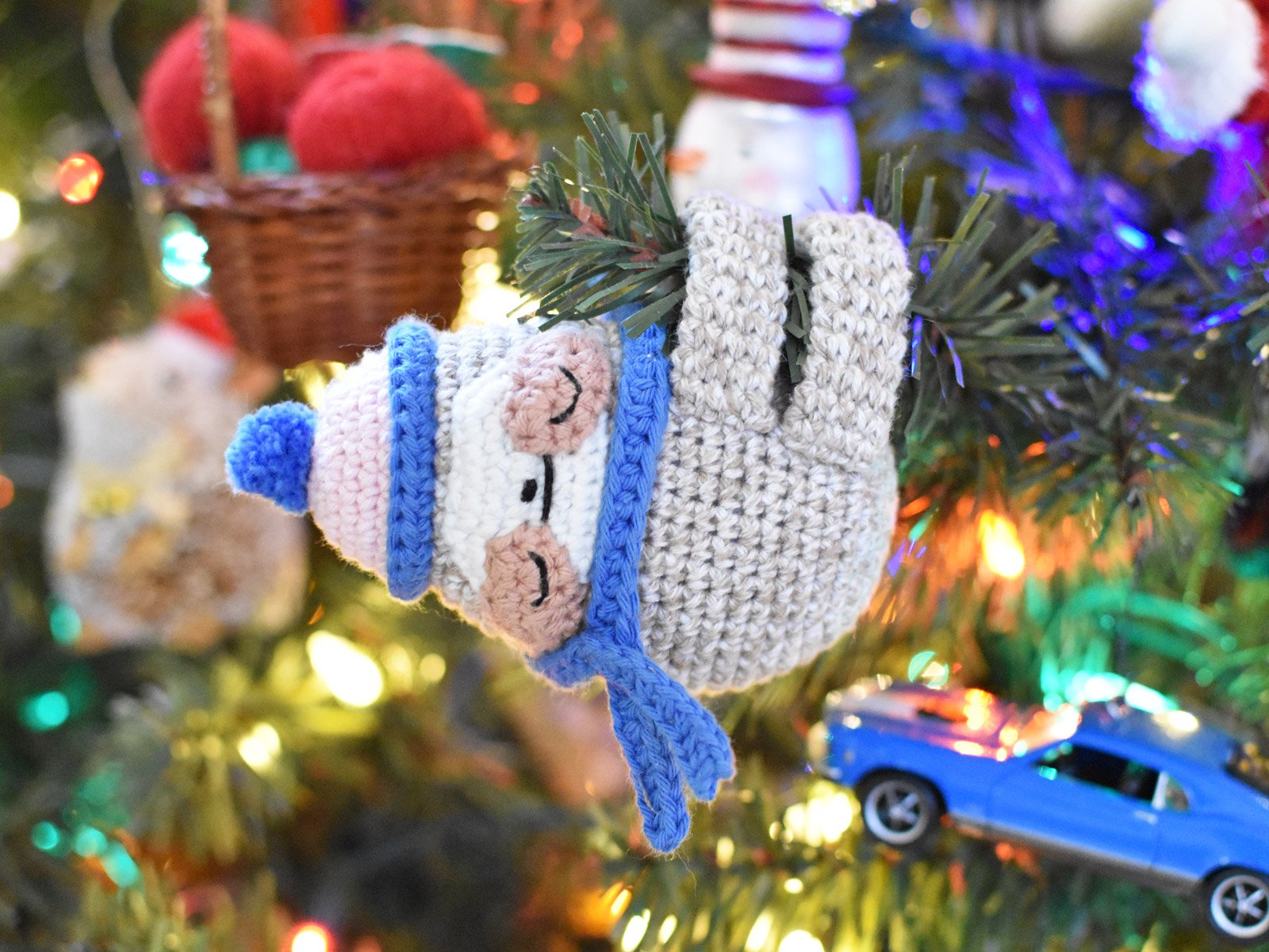 crochet sloth ornament hanging from Christmas tree with branch through the arm and leg loops
