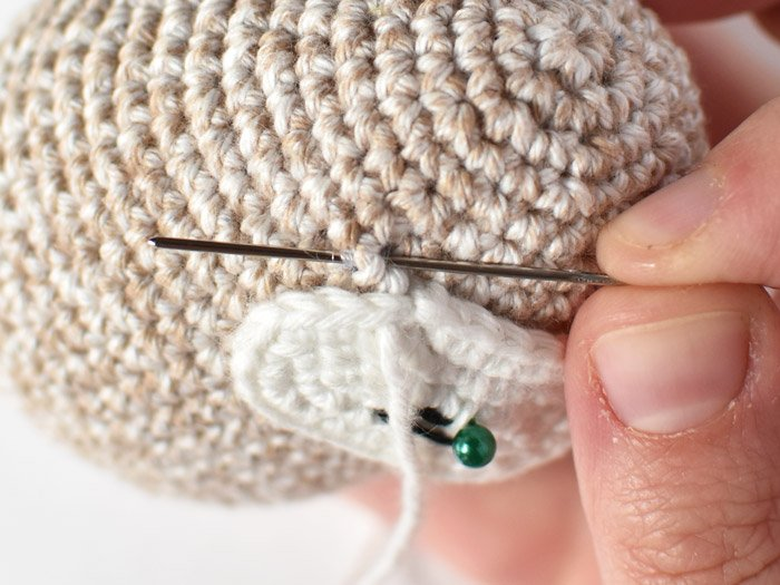 sewing the face to the amigurumi sloth