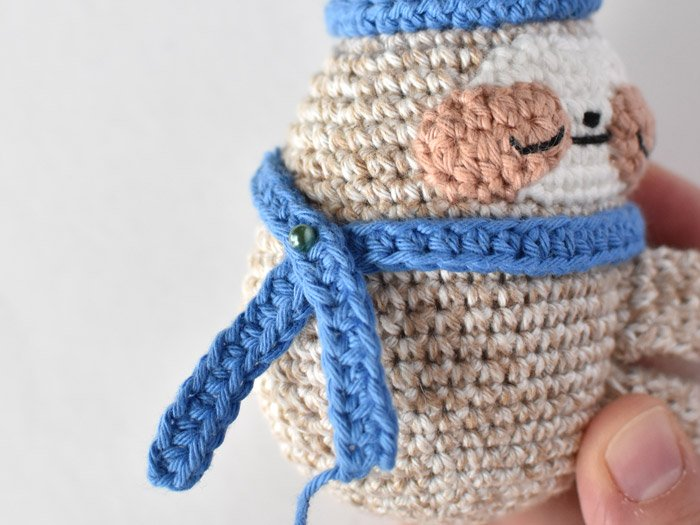 a blue crochet scarf wrapped around sloth's body with a pin securing it in place