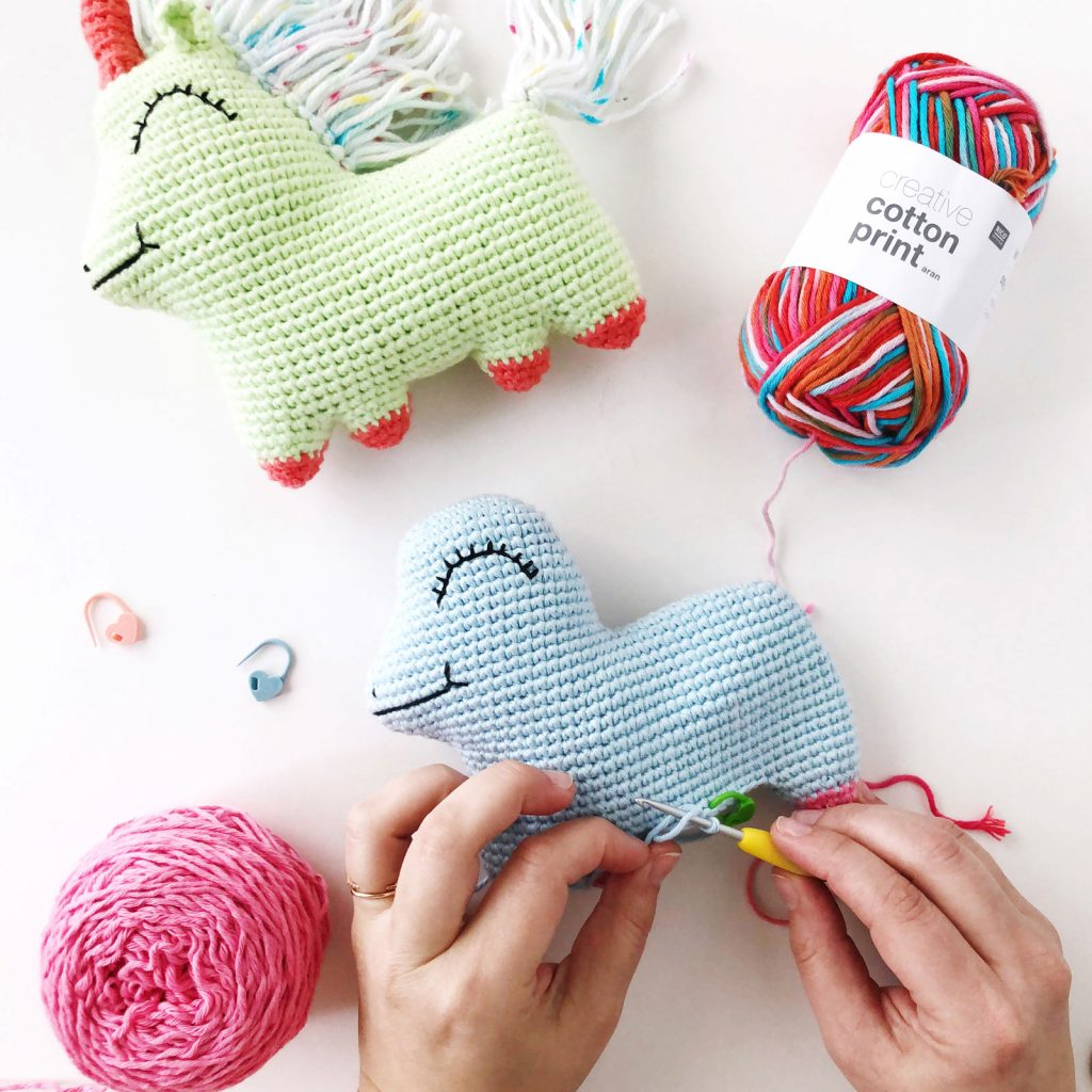Two hans are crocheting an amigurumi unicorn on a white background.